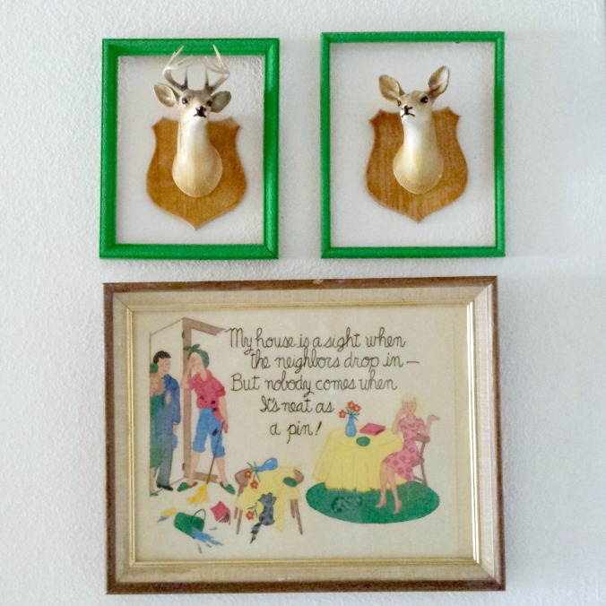 Upcycled vintage frames, plastic deer trophies, and a mid-century piece hanging in my entry way.